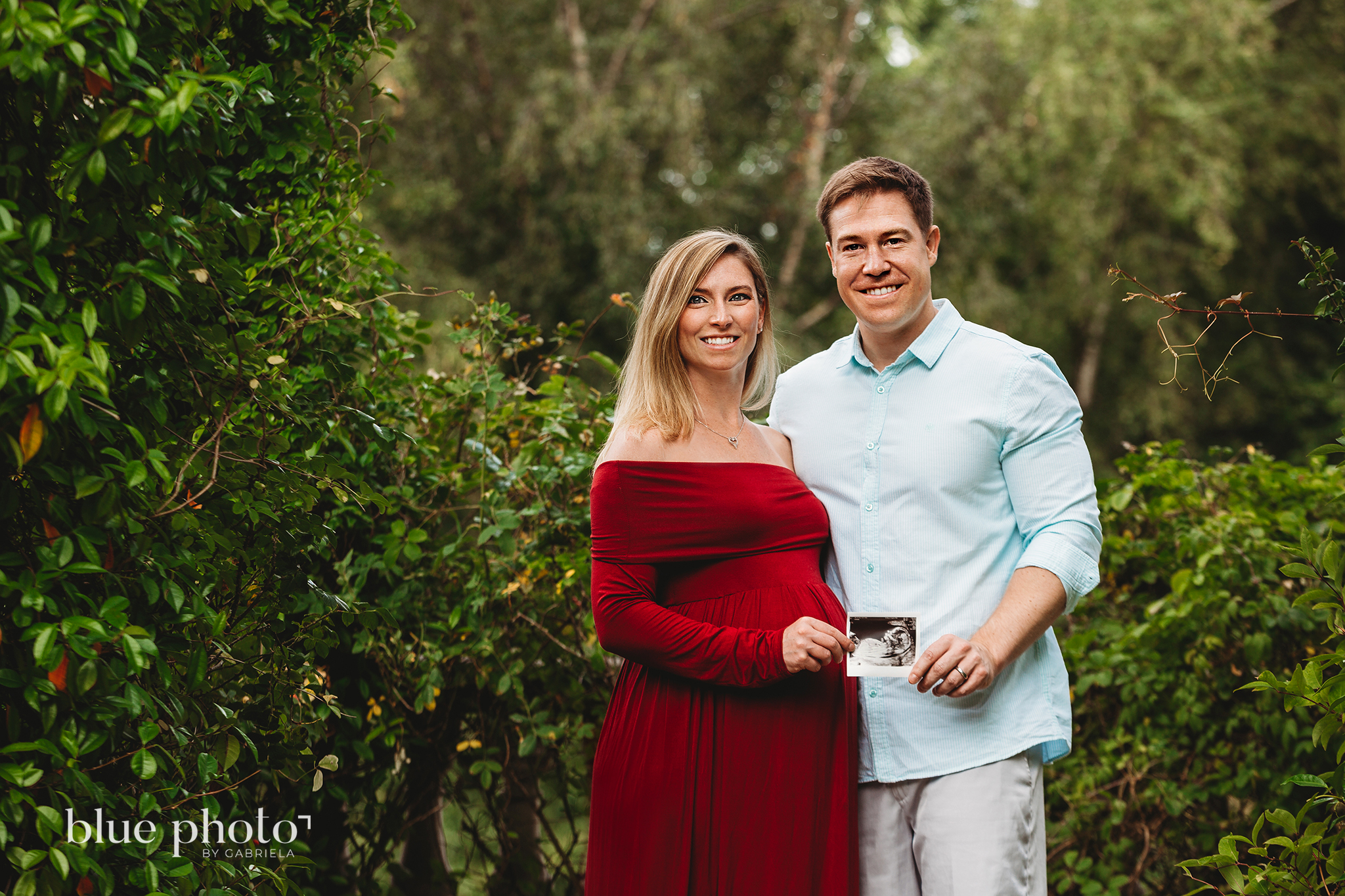 Maternity session in North London, couple is holding a USG picture in The Hill and Pergola Garden