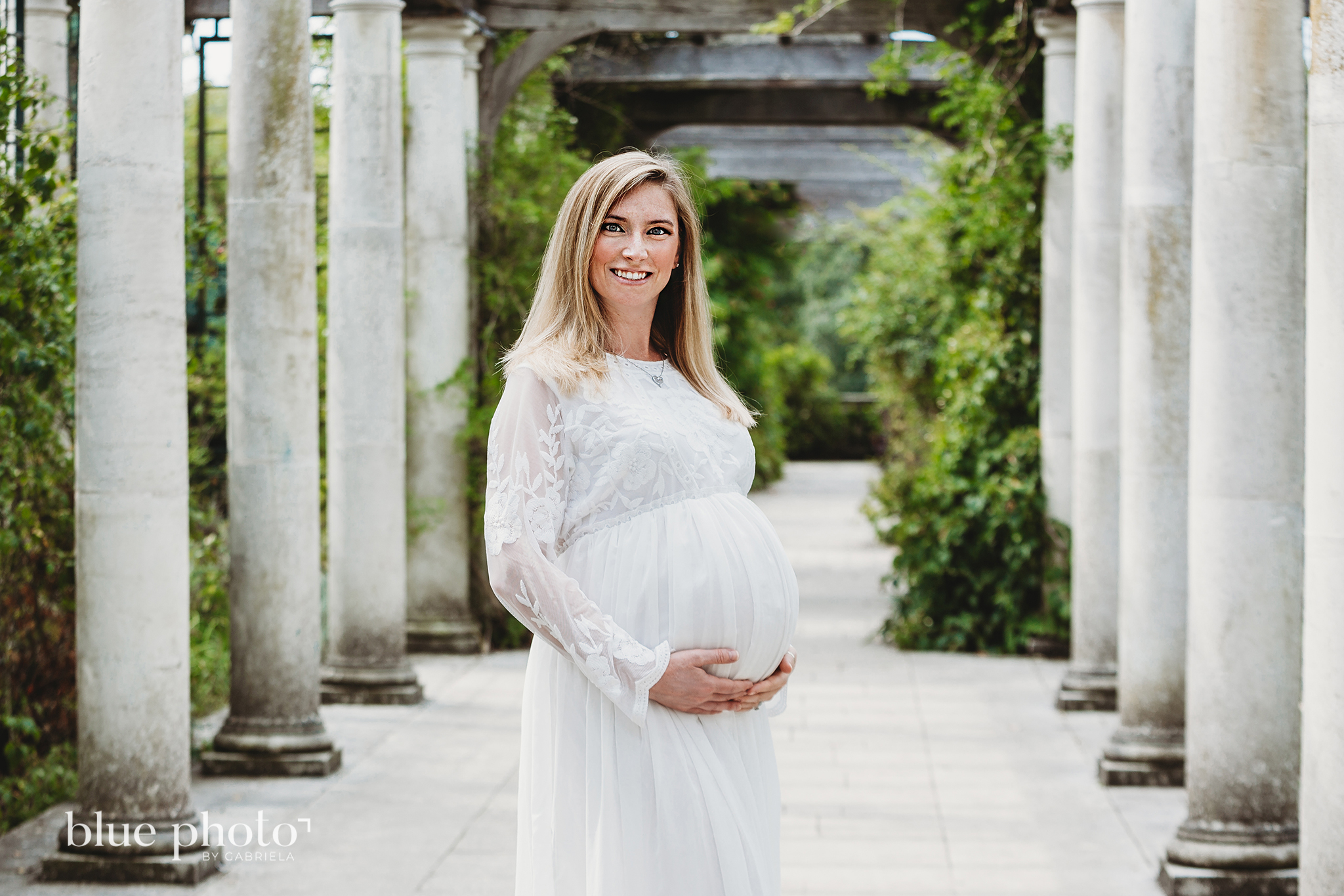 Maternity session in North London, a pregnant woman in white dress is possing in The Hill and Pergola Garden