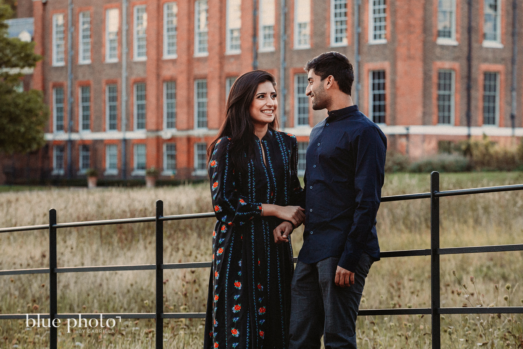 Engagement session in Kensingtom Gardens, Central London. A couple is looking at each other and smilling.