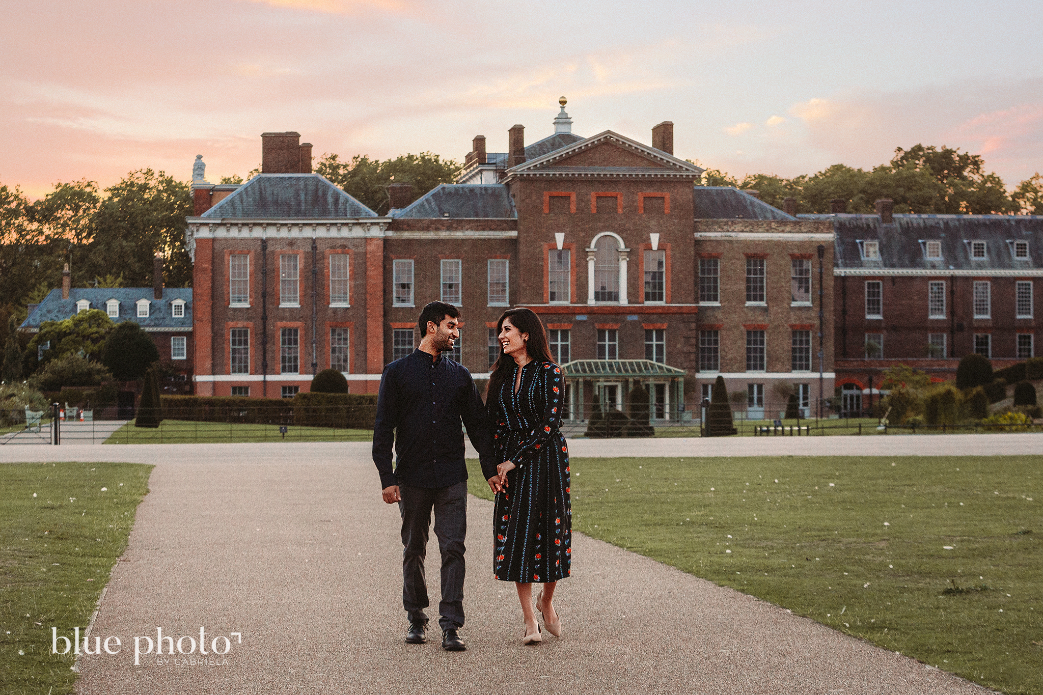 Engagement session in Kensingtom Gardens, Central London. A couple is walking, looking at each other and smilling.