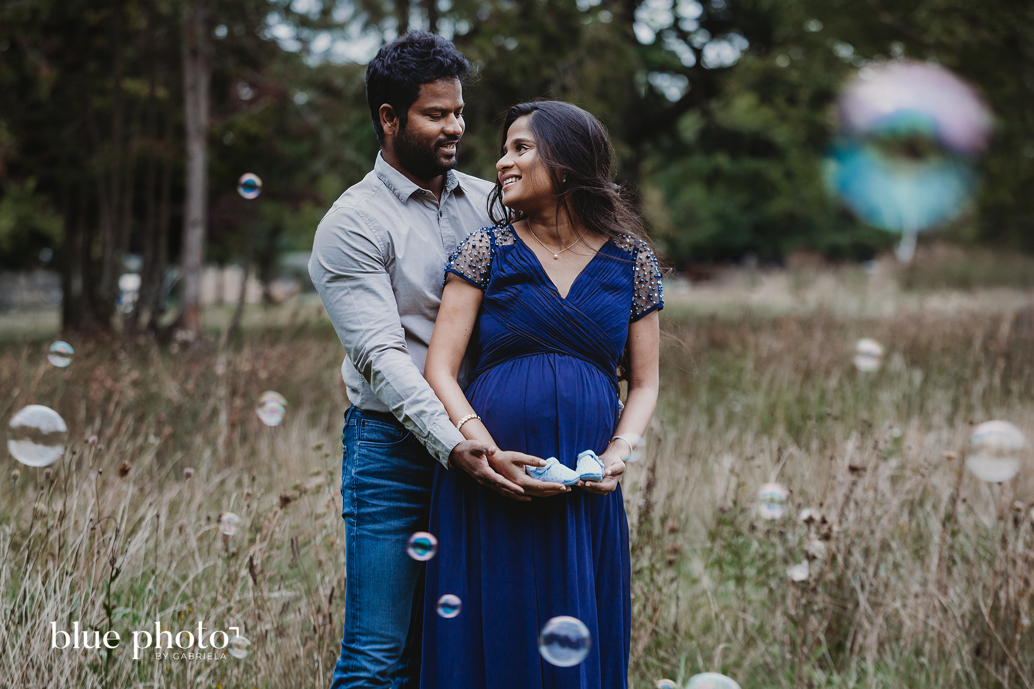 Socially distanced maternity session in West London. The couple is looking at each other and smiling.